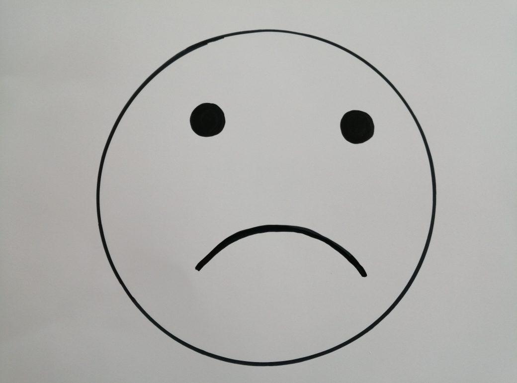 Auf weißem Blatt ist ein trauriges Smilie zu sehen